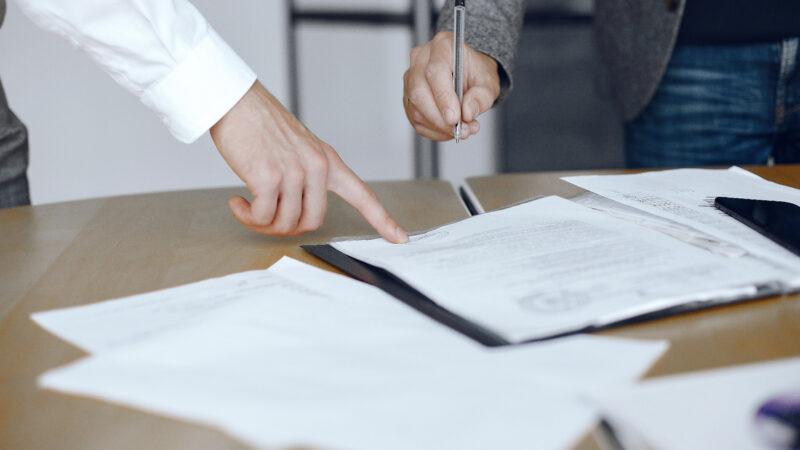Homens analisando papeis para explicar onde autenticar documentos